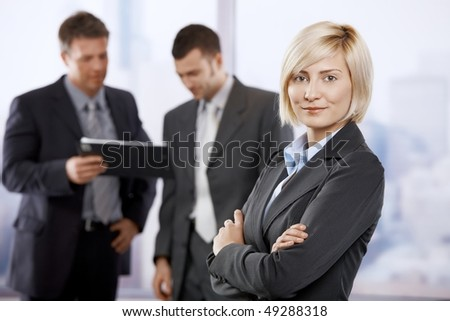 Portrait of confident businesswoman in office lobby, smiling. Colleagues talking in the background. - stock photo