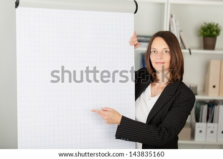Portrait of confident businesswoman pointing at flipchart in office - stock photo