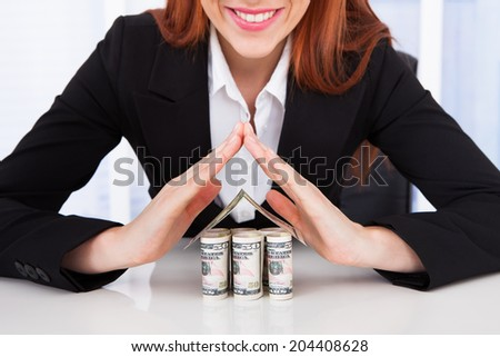 Portrait of confident businesswoman protecting house made of dollar bills at office desk - stock photo