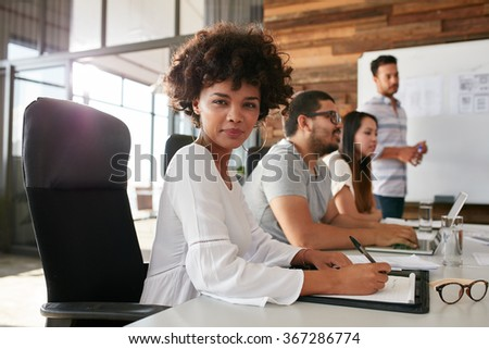 Portrait of confident businesswoman sitting at a business presentation with colleagues in boardroom. African woman with coworkers in conference room. - stock photo