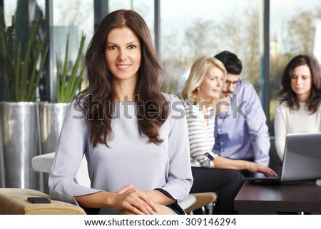 Portrait of confident businesswoman sitting at office and looking at camera while business people working at background with laptop. Teamwork at office.