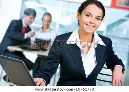Portrait of confident businesswoman sitting near table with laptop on it on the background of her working colleagues