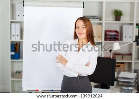 Portrait of confident businesswoman with arms crossed standing against flip chart - stock photo