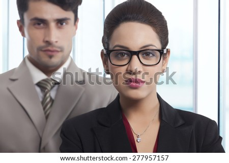 Portrait of confident businesswoman with colleague in office