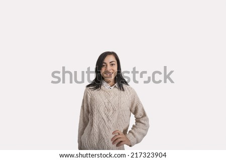 Portrait of confident businesswoman with hand on hip standing against gray background - stock photo