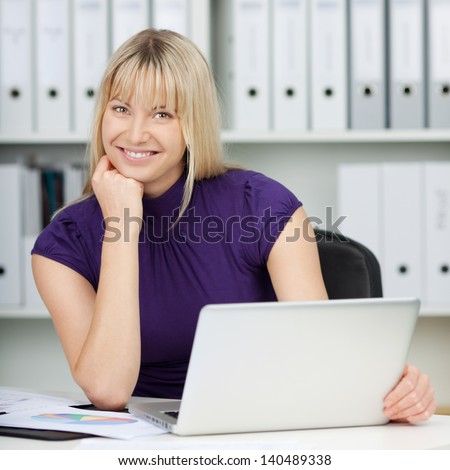 Portrait of confident businesswoman with laptop at office desk - stock photo