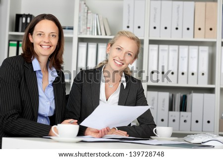 Portrait of confident businesswomen sitting at office desk - stock photo
