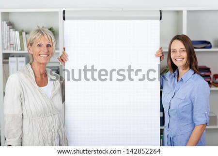 Portrait of confident businesswomen standing by flipchart in office - stock photo