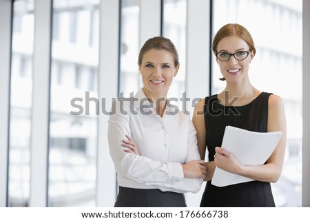 Portrait of confident businesswomen with documents in office - stock photo