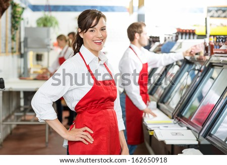 Portrait of confident butcher standing at store with colleagues working in background