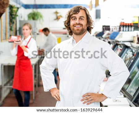 Portrait of confident butcher standing at store with colleagues working in background - stock photo