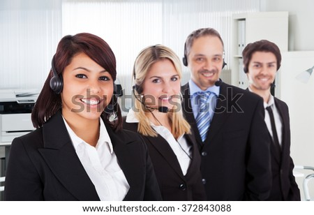 Portrait of confident call center representatives smiling in office - stock photo