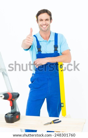 Portrait of confident carpenter leaning on spirit level while gesturing thumbs up over white background