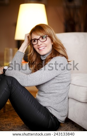 POrtrait of confident casual business woman sitting at home in living room. Shallow focus. - stock photo