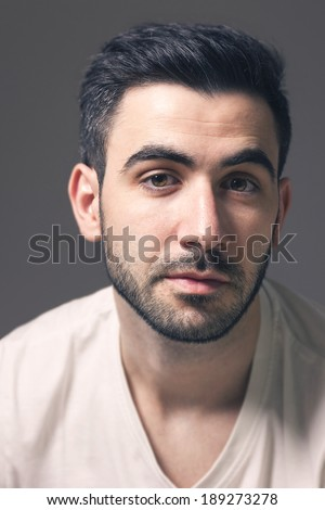 Portrait of confident caucasian male with beard looking to camera. Rembrandt lighting and grey background.