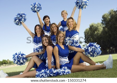 Portrait of confident cheerleaders holding pompoms on field - stock photo