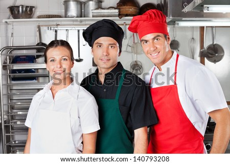 Portrait of confident chefs standing together in commercial kitchen - stock photo