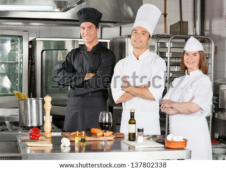 Portrait of confident chefs standing with arms crossed by kitchen counter - stock photo