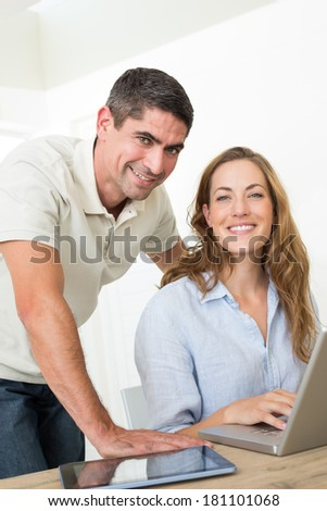 Portrait of confident couple using laptop at home