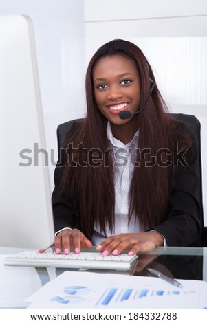 Portrait of confident customer service representative working at desk in office - stock photo