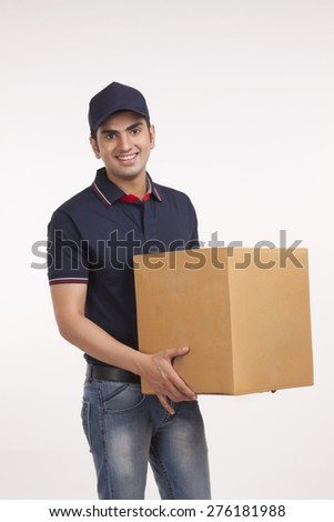 Portrait of confident delivery man carrying cardboard box against white background - stock photo