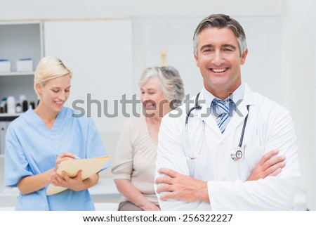 Portrait of confident doctor standing arms crossed while nurse and patient discussing in background at clinic