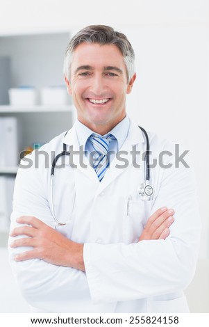 Portrait of confident doctor with arms crossed in clinic - stock photo