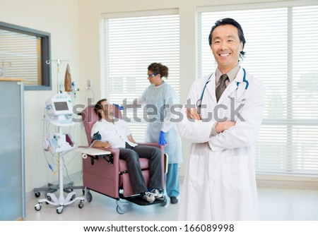 Portrait of confident doctor with female nurse looking at patient being examined by heartbeat machine in hospital - stock photo