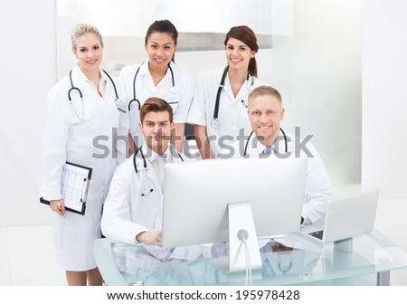 Portrait of confident doctors at desk in clinic - stock photo