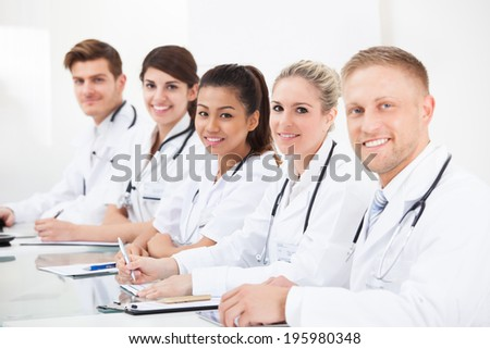 Portrait of confident doctors sitting in a row at desk - stock photo