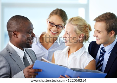 Portrait of confident employees looking at document at meeting - stock photo