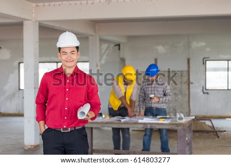 Portrait of confident engineer standing at front of labor and foreman as discussing with safety helmet on old buildings in their job site.