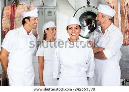 Portrait of confident female butcher with colleagues in butchery - stock photo