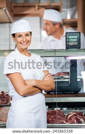 Portrait of confident female butcher with male colleague working in shop