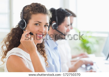 Portrait of confident female call center agent working in office - stock photo