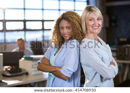 Portrait of confident female colleagues standing back to back in creative office - stock photo