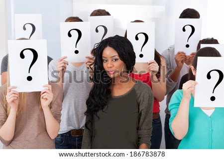 Portrait of confident female college student surrounded by classmates holding question mark signs in classroom - stock photo