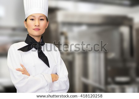 Portrait of confident female cook in kitchen against pots standing on hotplate - stock photo