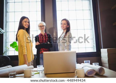 Portrait of confident female coworkers standing by desk in creative office - stock photo