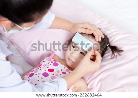 Portrait of confident female doctor paste cooling fever patch on forehead little asian girl during medical treatment, girl lying on sickbed and looking a doctor - stock photo