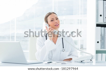 Portrait of confident female doctor using telephone at desk in clinic - stock photo