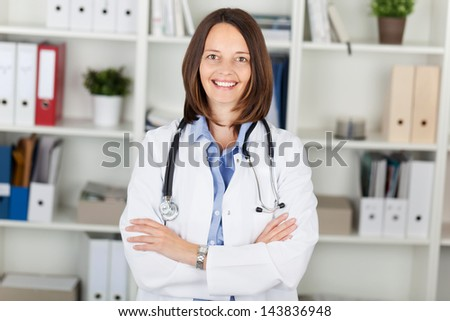 Portrait of confident female doctor with arms crossed standing against shelves in office