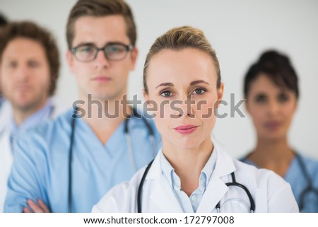 Portrait of confident female doctor with colleagues in hospital - stock photo