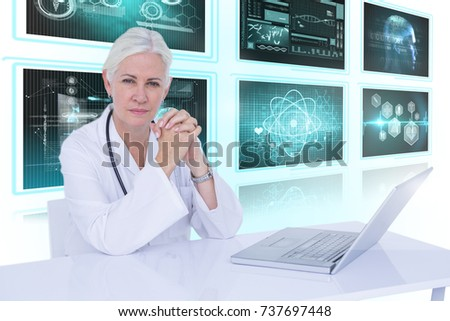 Portrait of confident female doctor with 3D laptop on desk against white background with vignette