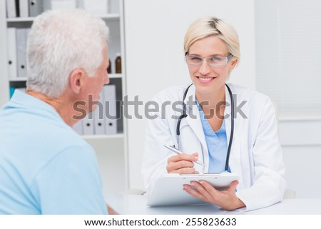 Portrait of confident female doctor writing prescription for senior man in clinic