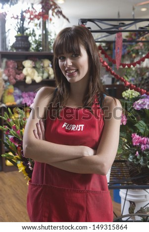 Portrait of confident female florist standing arms crossed in shop - stock photo
