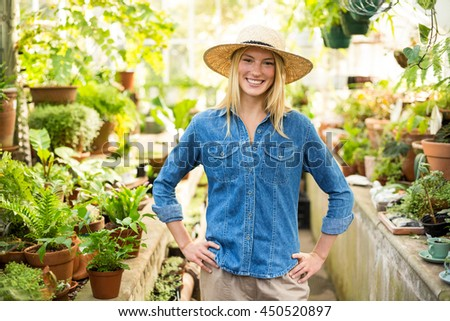 Portrait of confident female gardener at greenhouse