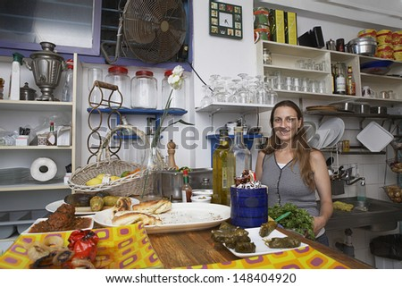 Portrait of confident female owner standing at counter in restaurant - stock photo
