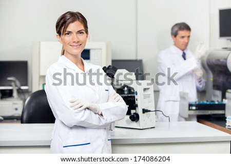 Portrait of confident female scientist with colleague in background at laboratory - stock photo