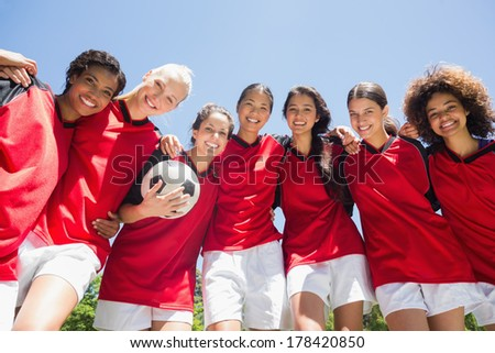 Portrait of confident female soccer team with ball against clear blue sky - stock photo